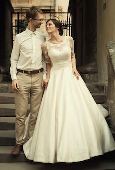 Sposa e sposo felici romantici di lusso che celebrano il matrimonio sullo sfondo della vecchia città soleggiata