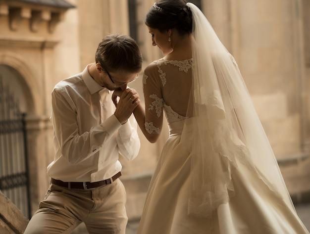 Sposa e sposo felici romantici di lusso che celebrano il matrimonio sulla superficie della vecchia città soleggiata