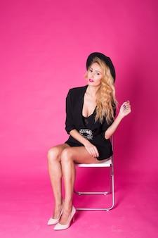 Concetto di lusso, stile e persone - bella donna sexy in un cappello nero con labbra rosa e vestiti alla moda.