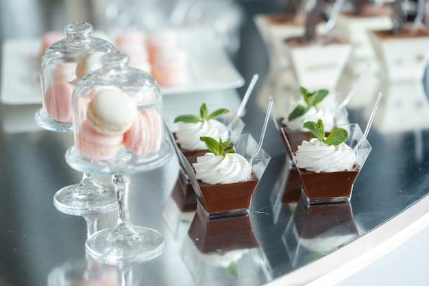 Dessert dolci di lusso al matrimonio. macarons e dessert al cioccolato in forme di vetro Foto Premium