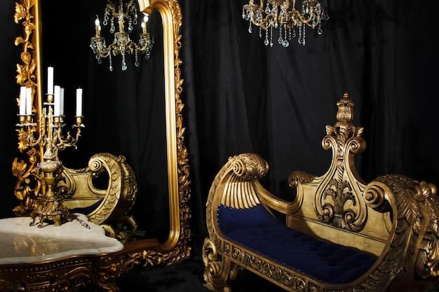 Interiore della stanza di casa vintage di lusso in nero e oro. soggiorno con specchio, divano e candelabri