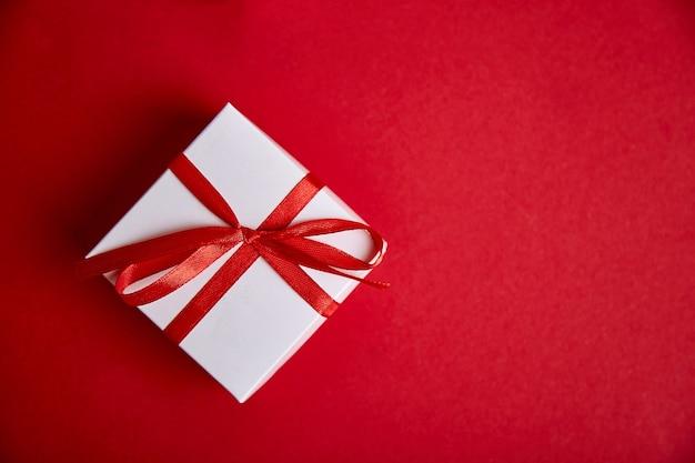 Contenitori di regalo bianchi di lusso con il nastro rosso sul rosso. v