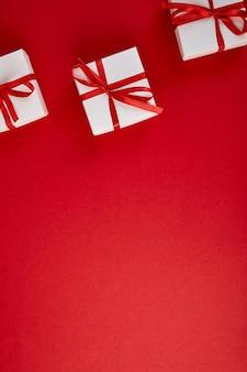 Contenitori di regalo bianchi di lusso con il nastro rosso sul rosso.