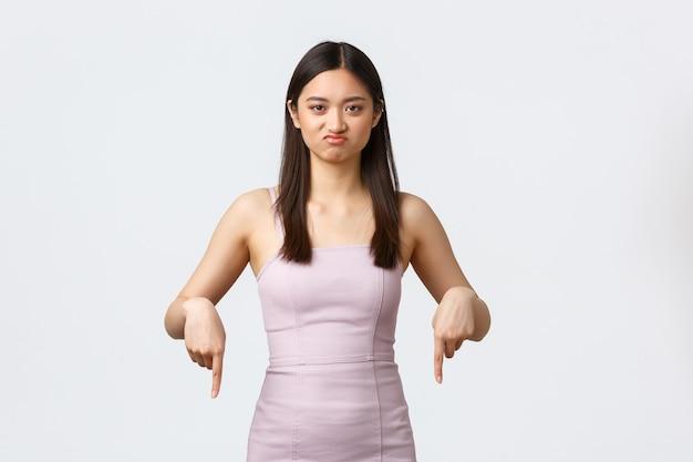 Donne di lusso, festa e concetto di vacanze. ragazza asiatica carina schizzinosa e scettica in abito da sera