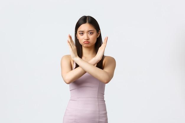 Donne di lusso, festa e concetto di vacanze. la donna asiatica seria in vestito da sera che fa gesto trasversale, dice di fermarsi