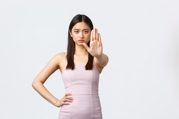 Donne di lusso, festa e concetto di vacanze. donna asiatica seria e determinata in abito da sera che dice di fermarsi, dire basta o no