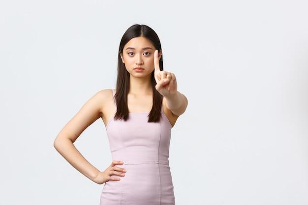 Donne di lusso, festa e concetto di vacanze. non così in fretta. donna asiatica dall'aspetto serio in abito da sera che agita il dito in segno di diniego, rifiuto o divieto