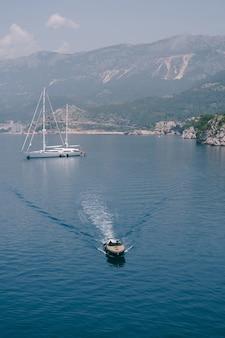 Una lussuosa barca a motore sportiva in legno trasporta i vip da una grande barca bianca attraccata al largo della costa di