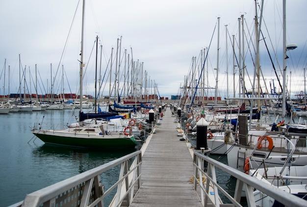 Yacht e barche di lusso nel porto di valencia al mar mediterraneo. riflessione nell'acqua. gli yacht bianchi si trovano nel porto spagnolo di valencia all'inizio della primavera. cielo nuvoloso.