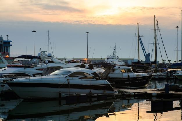 Yacht di lusso ancorati nel porto marittimo al tramonto. parcheggio marittimo di moderne barche a motore e acque blu.