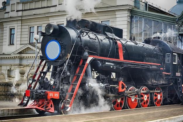 Lviv, ucraina - dicembre 2015: il vecchio treno retrò nero vintage sovietico l-3535 presso la stazione ferroviaria di lviv produce vapore dai tubi
