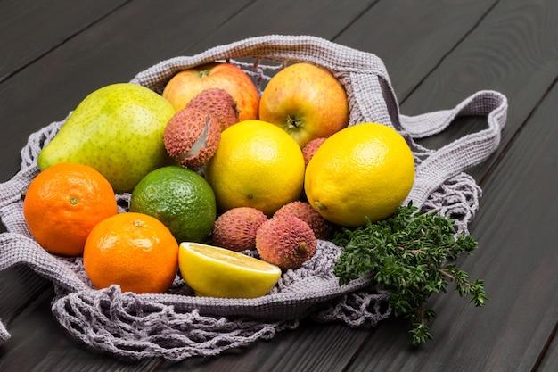 Litchi, pera, mele e limone in sacchetto a rete riutilizzabile. fondo in legno scuro. vista dall'alto