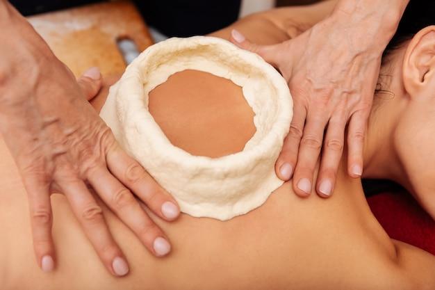 Sdraiato nudo. lavoratrice professionista del salone spa che usa le mani per modellare la costruzione prima della sessione insolita
