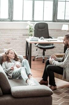 Sdraiato sul divano. adolescente alla moda riccio sdraiato sul divano e parlando con il suo attento terapista privato