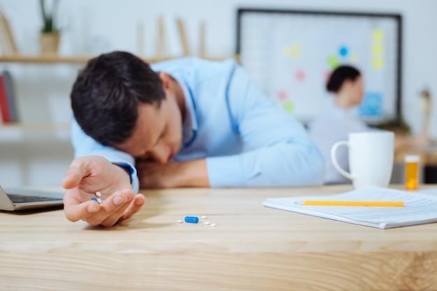 Sdraiato sul tavolo. uomo malato che dorme mentre era seduto in ufficio e appoggiato sul tavolo
