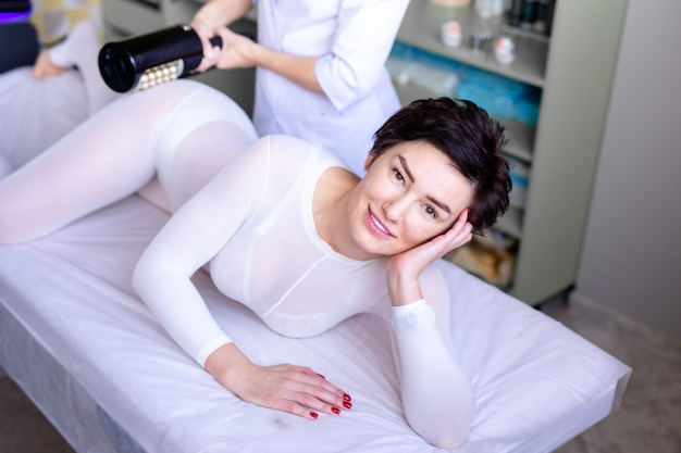Massaggio linfodrenante processo apparecchio gpl o r-sleek. donna in vestito bianco che ottiene massaggio anticellulite in un salone di bellezza. cura della pelle e del corpo.
