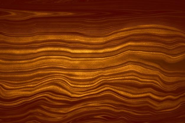 Fondo di struttura del bronzo dell'oro rosso scuro minerale del metallo e di mable