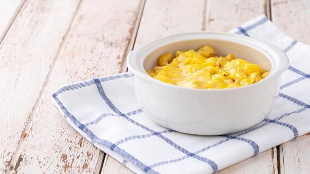 Mac e formaggio, pasta di maccheroni con formaggio in ciotola di ceramica su tovagliolo su fondo di legno bianco vecchio