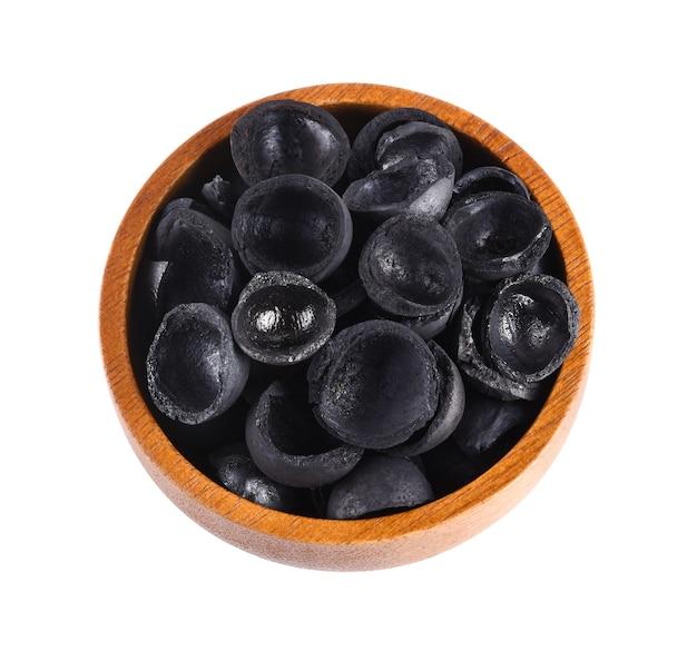 Carbone di macadamia su ciotola di legno isolato su sfondo bianco