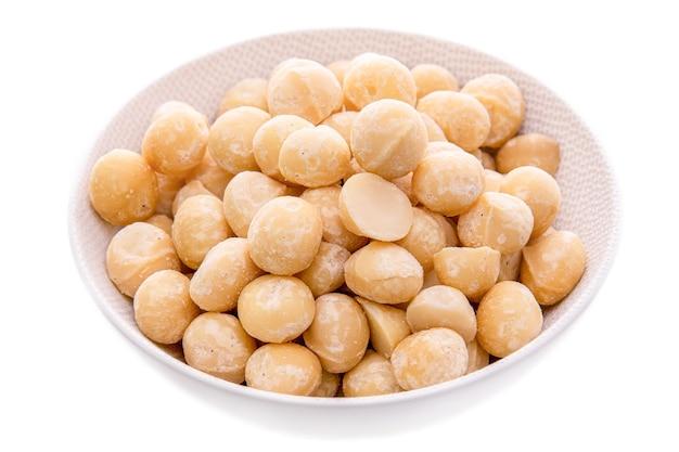 I noccioli di noce di macadamia in un piatto bianco su uno sfondo bianco hanno isolato oggetti e prodotti