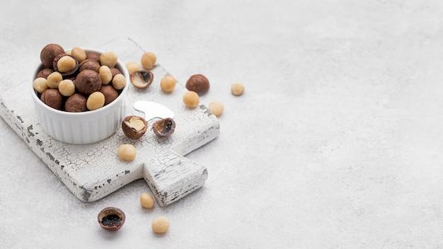 Noci di macadamia all'interno di rotoli di cioccolato sullo spazio della copia del tagliere
