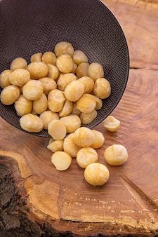 Noci di macadamia versate da una tazza scura su un tavolo di legno