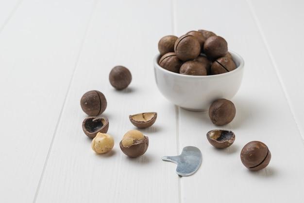 Noci di macadamia in una ciotola in ceramica bianca su un tavolo di legno bianco. superfood.
