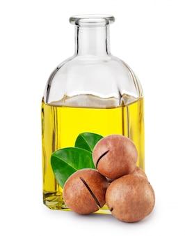 Olio di macadamia in bottiglia e noci con foglie