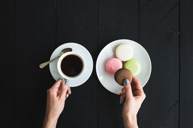 Biscotti macaron, tazza di caffè espresso e mani da donna