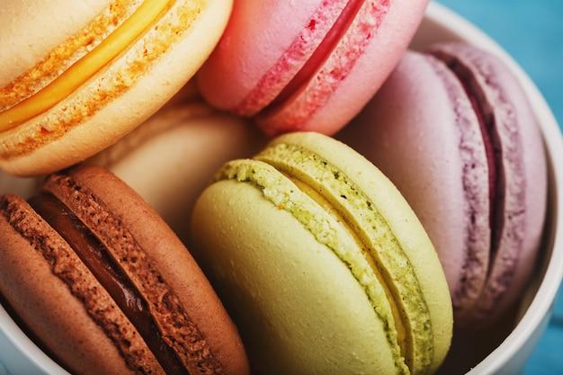 Biscotti di macaron con il primo piano di riempimento di colore differente, macro.