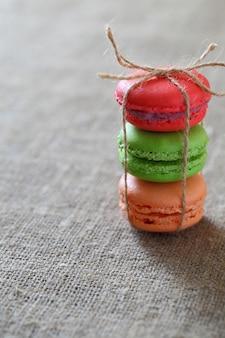 Macaron tre pezzi rosso, verde e arancio legati con una corda sulla tovaglia di tela. telaio verticale.