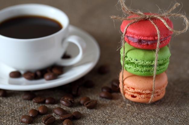 Macaron tre pezzi rosso, verde e arancio legati con corda e tazza di caffè, fagioli sparsi e piattino sulla tovaglia di tela.