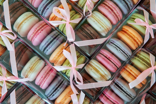 Biscotti di maccheroni di diversi colori in un pacchetto con fiocco, molte scatole con biscotti a forma di trama.