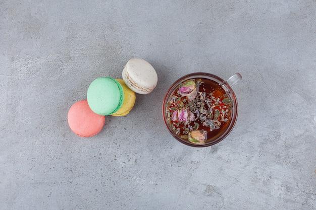 Biscotti maccheroni di diversi colori con una tazza di vetro di tisana.