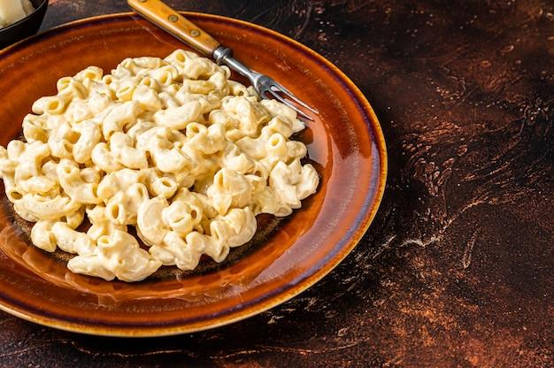 Maccheroni mac e formaggio con salsa di cheddar in un piatto. sfondo scuro. vista dall'alto. copia spazio.