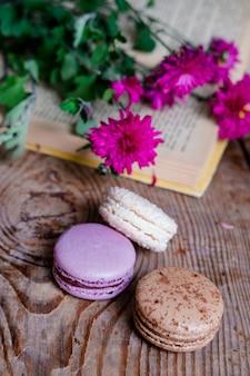 Macarons sfondo fiori rossi e libri, su un tavolo di legno. cornice verticale. estetica con amaretti e fiori. bellissime torte su un tavolo di legno. mattina colazione francese.