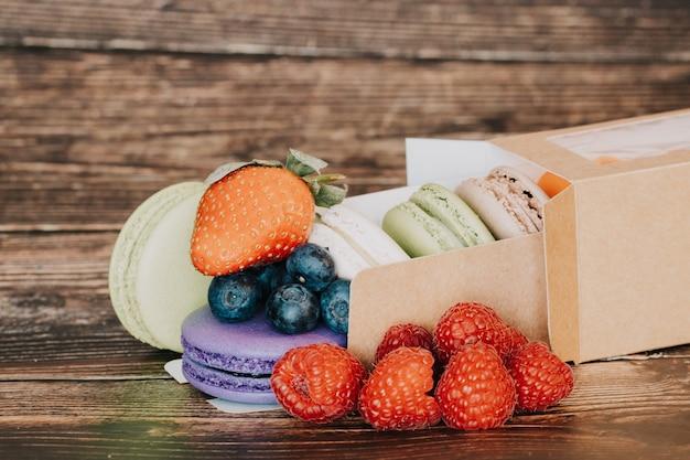 Macarons e lamponi frutti di bosco, mirtilli su una superficie di legno