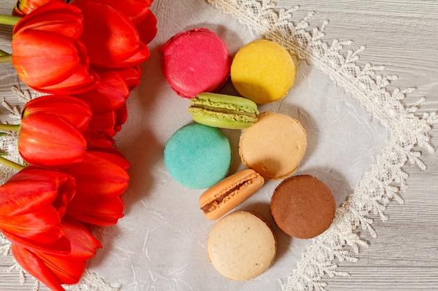 Torte di macarons di colore diverso su tovagliolo di seta con bouquet di tulipani rossi freschi con fondo in legno. vista dall'alto