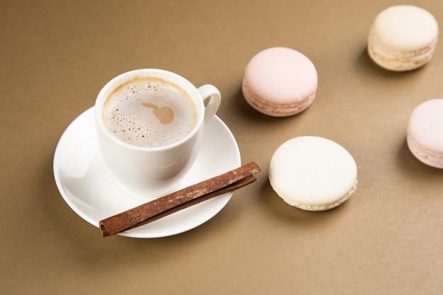 Macarons e caffè con cannella su una superficie grigia.