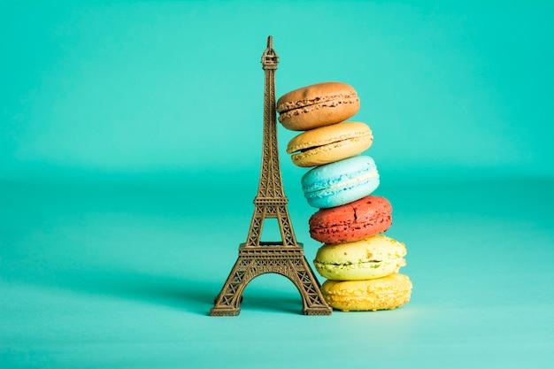 Macarons di diversi sapori ricaricati sulla torre eiffel su un turchese