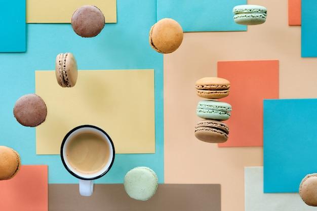 Macarons ed espresso, piatto disteso su sfondo di carta geometrica