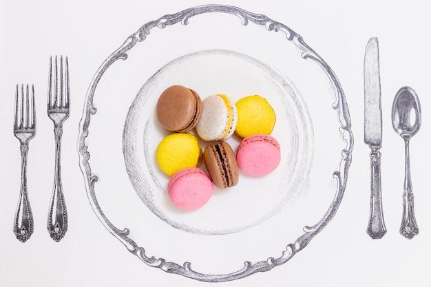 Macarons serviti su un piatto accanto a una forchetta alta e piccola
