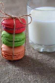 Macarons tre pezzi rossi, verdi, arancioni legati con una corda e un bicchiere di latte sulla tovaglia di tela.