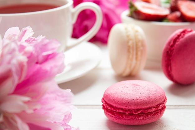 Macarons con il tè alla frutta delle fragole e il primo piano delle peonie su una tavola di legno bianca fuoco selettivo