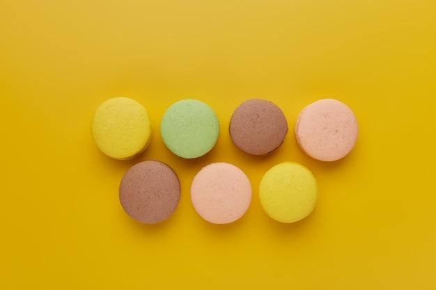 Amaretto. i macaron di torta colorati con toni pastello sono sfalsati su sfondo giallo. vista dall'alto di biscotti alle mandorle.