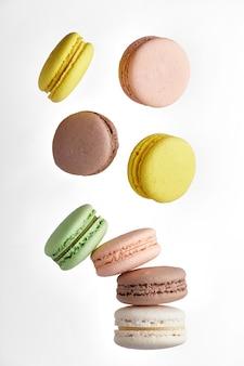 Amaretto. macaron torta colorata con toni pastello cadono al maccherone pila sul muro bianco. vista dall'alto di biscotti alle mandorle.
