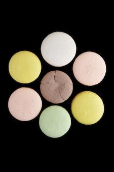 Amaretto. sei macaron colorati con toni pastello e uno incrinato giacevano a forma di fiore sulla superficie nera. vista dall'alto di biscotti alle mandorle.