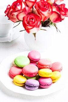 Amaretti sul piatto e rose in vaso. tabella di compleanno