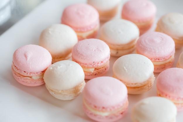 Amaretti su un piatto quadrato bianco. delizioso dessert per il matrimonio. sfondo pastello morbido.