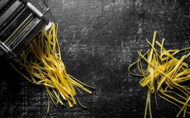 Macchina per la cottura della pasta fatta in casa. sul nero rustico